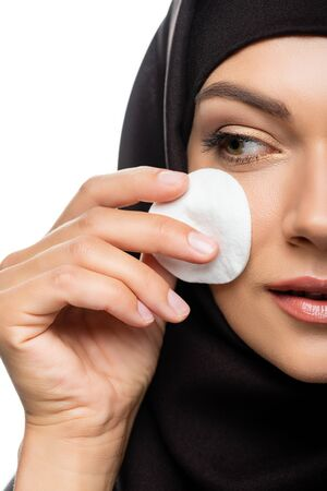 cropped view of young Muslim woman in hijab wiping face with cotton pad isolated on white Stock fotó
