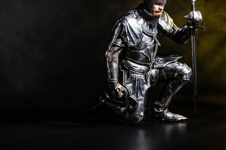 handsome knight in armor holding sword and bend knee on black background Archivio Fotografico - 134657475