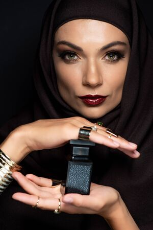 beautiful Muslim woman in hijab with makeup in golden jewelry holding perfume isolated on black Stock fotó