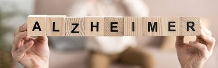 panoramic shot of senior woman holding wooden cubes with alzheimer letters