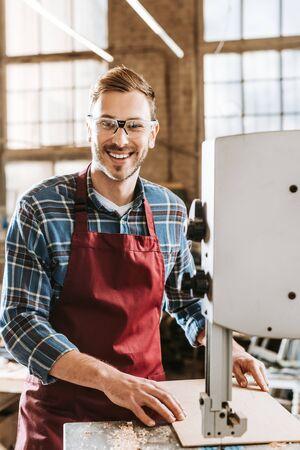cheerful carpenter in goggles standing near cnc machine Stock Photo