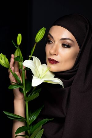attractive Muslim woman in hijab with red lips holding lily isolated on black