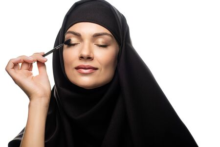 young Muslim woman in hijab applying mascara on eyelashes with closed eyes isolated on white Stock fotó