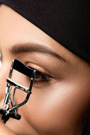 close up view of young Muslim woman in hijab using eyelash curler