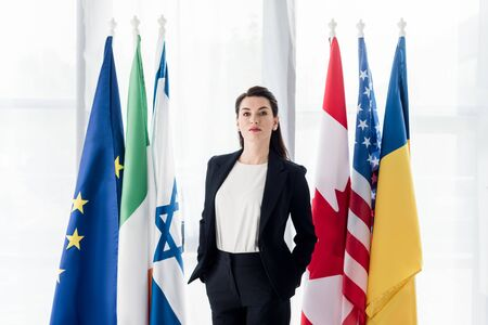 Attraktiver Diplomat, der mit den Händen in den Taschen in der Nähe von Flaggen steht