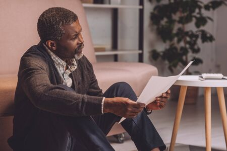 upset african american man sitting on floor and looking at utility bill