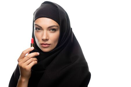young Muslim woman in hijab holding red lipstick isolated on white Stock fotó