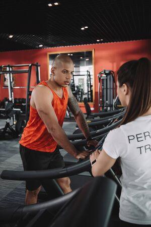 personal trainer standing near african american sportsman running on treadmill 版權商用圖片