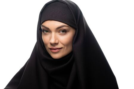 smiling beautiful young Muslim woman in hijab looking at camera isolated on white
