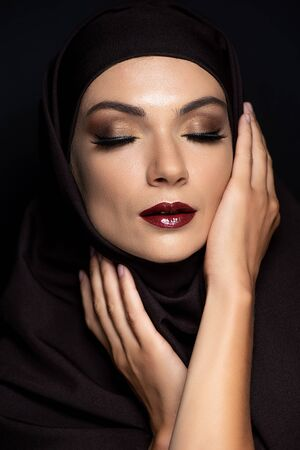 young Muslim woman in hijab with closed eyes, smoky eyes and red lips isolated on black