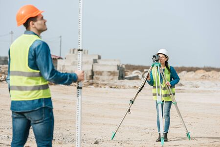 Selective focus of surveyors using digital level and ruler on construction site