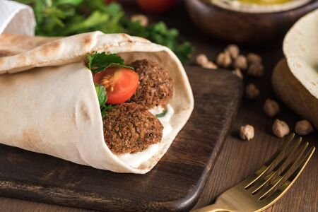 close up view of falafel with vegetables and sauce wrapped in pita on wooden table