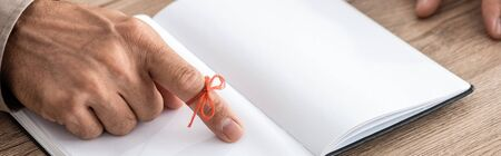 panoramic shot of senior man with red bow on finger as reminder near notebook
