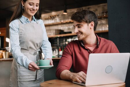 smiling waitress serving coffee to freelancer with laptop