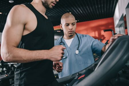 cropped view of sportsman on treadmill near attentive african american doctor Stock Photo