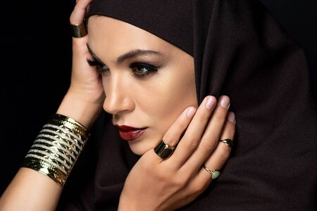 beautiful Muslim woman in hijab with makeup in golden rings and bracelet isolated on black Stock fotó