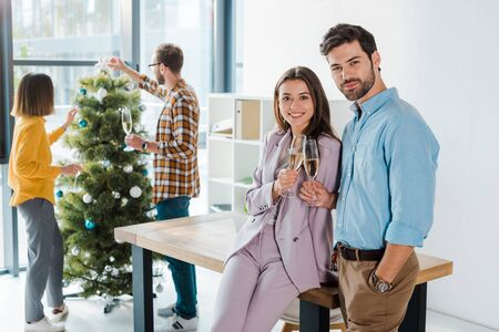 selective focus of businessman and businesswoman toasting champagne glasses near colleagues and christmas tree Фото со стока