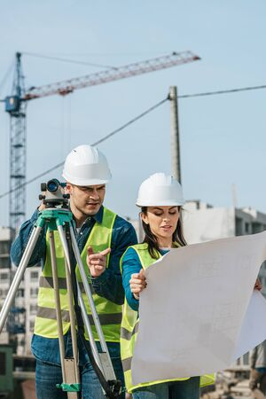 Surveyors with digital level looking at blueprint on construction site Stock fotó