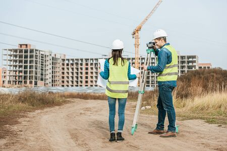 Surveyors working with blueprint and digital level on dirt road Stock fotó