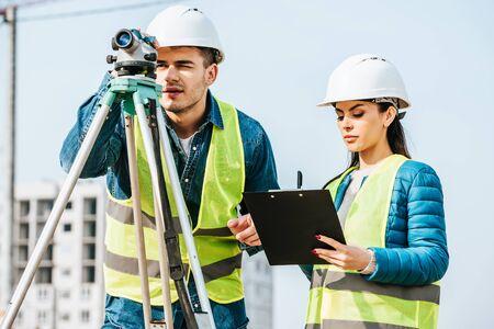 Surveyor using digital level while colleague writing on clipboard Stock fotó