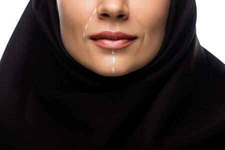 cropped view of young Muslim woman in hijab having marks on face for plastic surgery isolated on white Stock fotó