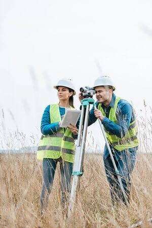 Surveyors working with digital level and using tablet in field