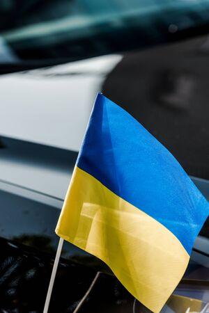 close up on ukrainian flag near black modern car Banco de Imagens
