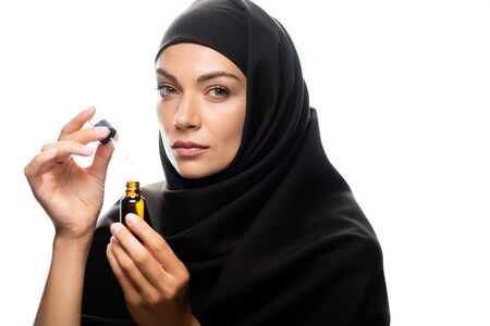 young Muslim woman in hijab holding dropper an bottle with serum isolated on white