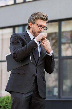 diplomate avec des lunettes fumant la pipe près du bâtiment à l'extérieur Banque d'images