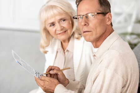selective focus of sick senior man with alzheimer holding pencil near crossword and wife