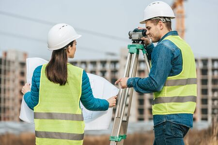 Surveyors working with blueprint and digital level