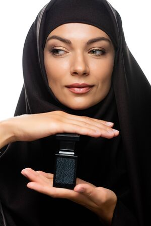 young Muslim woman in hijab holding bottle of perfume isolated on white Stock fotó