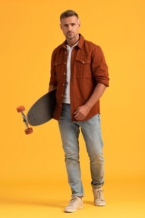 handsome man standing and holding penny board on orange