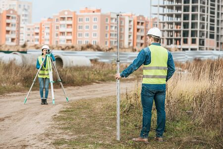 Surveyors measuring land with digital level and ruler