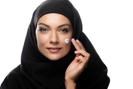 young Muslim woman in hijab applying cosmetic cream on chick isolated on white