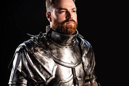 Schöner Ritter in Rüstung, der isoliert auf Schwarz wegschaut Standard-Bild