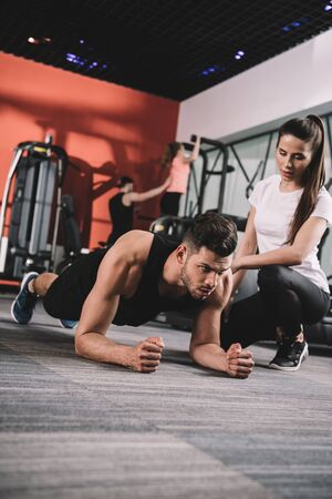 attentive trainer supervising young sportsman doing plank exercise Stock Photo
