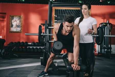 attractive trainer assisting handsome sportsman working out with dumbbell