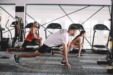 handsome trainer doing lunges exercise together with multicultural athletes