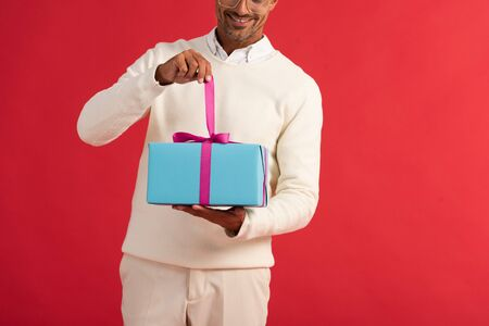 cropped view of happy man holding gift box isolated on red