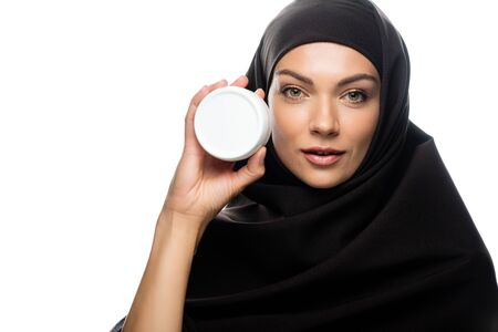 young Muslim woman in hijab holding container with cosmetic cream isolated on white