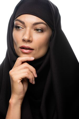beautiful young Muslim woman in hijab touching chin and looking away isolated on white Stock fotó