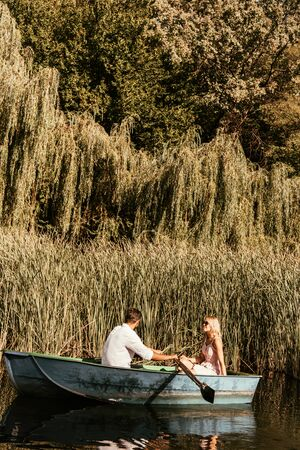 young couple in boat on lake near thicket of sedge Banque d'images
