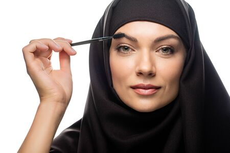young Muslim woman in hijab applying mascara on eyelashes isolated on white