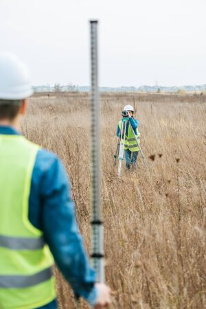 Selective focus of surveyors with digital level and ruler working in field