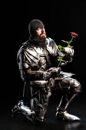 handsome knight in armor holding rose and bend knee on black background Archivio Fotografico - 134659806