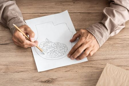 cropped view of retired man with alzheimer disease drawing human head and brain