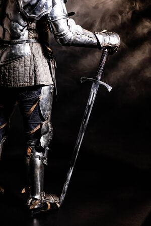 cropped view of knight in armor holding sword on black background Zdjęcie Seryjne