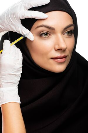 young Muslim woman in hijab having beauty injection isolated on white Stock fotó