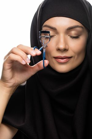 young Muslim woman in hijab using eyelash curler with closed eyes isolated on white